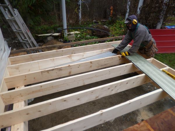 Metal siding is cut to size and put between each joist to hold the insulation