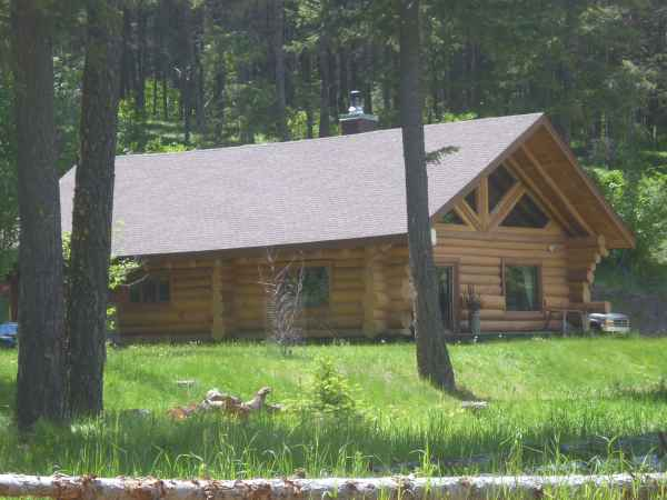 Hand built log home surrounded by woods